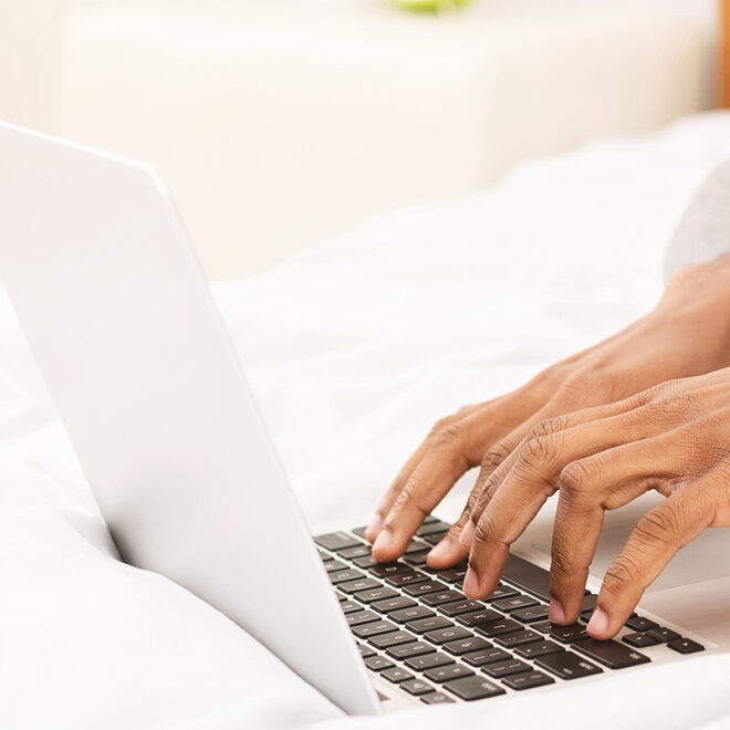 African-american programmer typing on laptop in bed