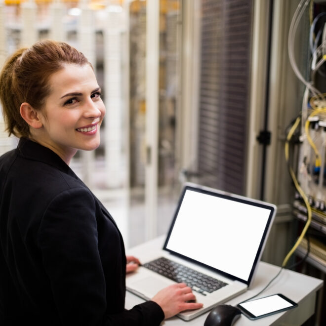 Technician using laptop while analyzing server